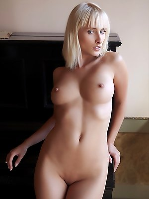 Colette bares her curvy body and sweet pussy beside the piano.