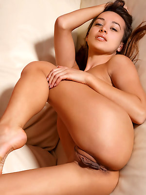 Alluring Dominika A strips on the couch as she bares her delectable